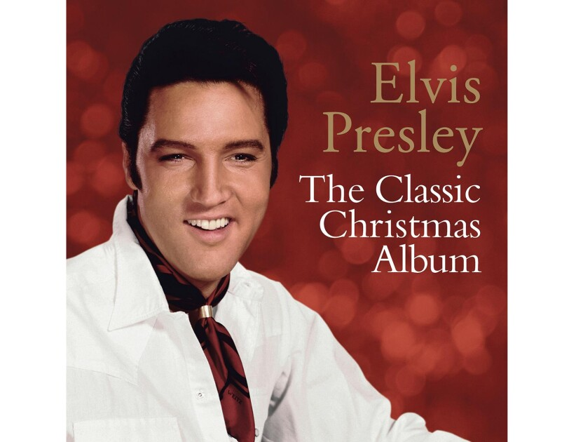 Elvis Presley wears a white button down and burgundy neck kerchief with a gold clasp. Behind him, we see out-of-focus lighting against a red background.