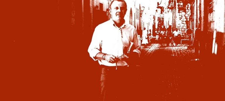 Photographie sépia de Patrick Philippart se tenant debout dans la rue d'un village, un livre à la main. Au loin derrière lui des silhouettes de personnes également dans la rue.