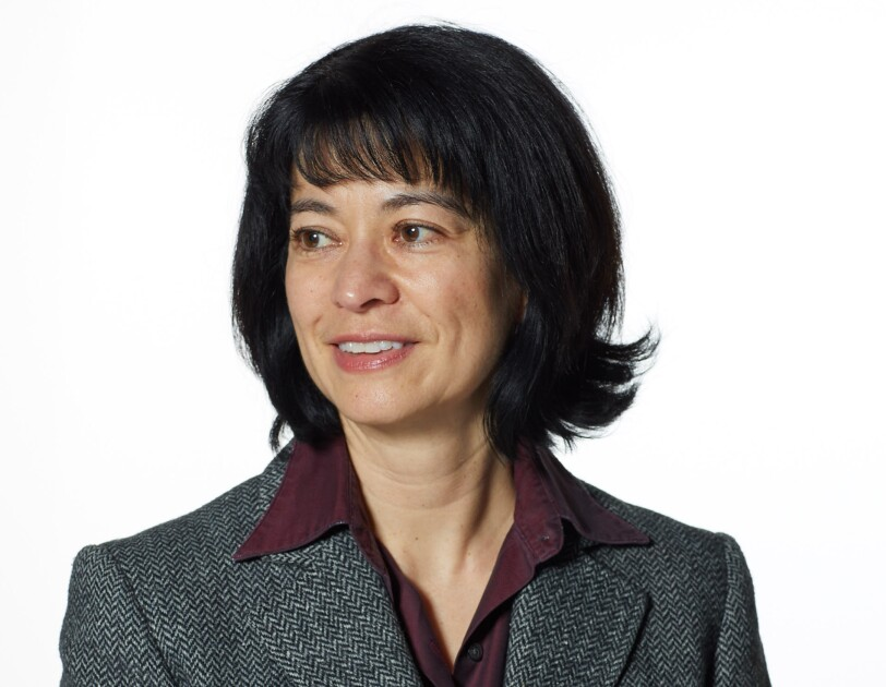 A headshot of Jacqui Chin wearing a greay blazer and looking to the left.