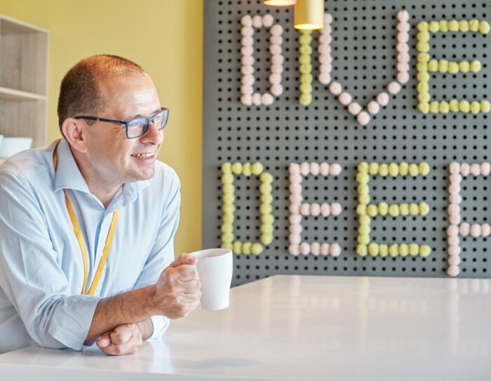 Federico Finzi, Legal Director di Amazon Italia e bar raiser, sorride e regge una tazza di caffé nella cucina dell'ufficio