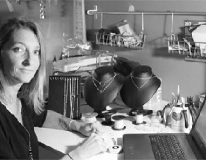 La fondatrice d'EmmaFashionNow se tient devant une table où se trouvent des bijoux finis ou en cours de création ainsi que son ordinateur. C'est une photo noir et blanc.