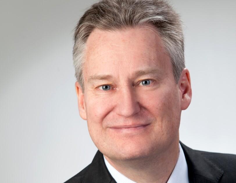 Porträtaufnahme eines Herrn in Anzug und Krawatte.