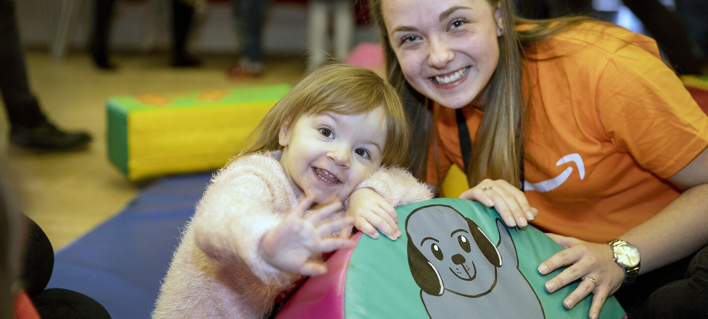 Bethan, a toddler with congenital Heart Disease and an Amazon worker from the Tilbury fulfilment centre, smile at the camera.