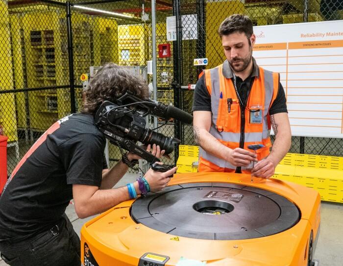 Raúl Cruz, técnico senior de mantenimiento en robótica, en un momento de la grabación mientras manipula un robot. En primer plano está Raúl, con el pelo negro y barba, vestido con una camiseta negra y el chaleco naraja. En la mano tiene una herramienta para abrir un robot. A su lado derecha aparece el cámara, vestido de negro grabando la reparación.