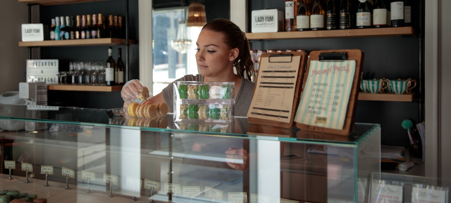 A woman stands behind the counter of a shop and places baked goods in a to-go container.
