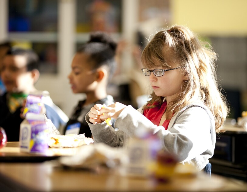 A young girl is opening preparing to eat. Behind her, other students are also eating. Apples and single-serve milk containers are on the desks in front of the students.
