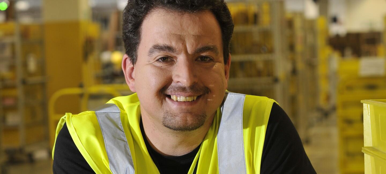 Nikolai Lisac, ein Mann mit Sicherheitsweste und braunem, gelocktem Haar, lehnt locker an einen Stapel von gelben Behältern in einem Logistikzentrum