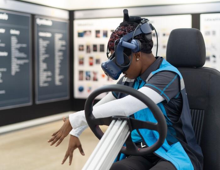 Riggins, una conductora, con unas gafas de realidad virtual pudo ver los recursos digitales. Es de color negro, tiene el pelo corto y lleva pendientes de perlas. Está sentada en un prototitpo de asiento de coche de Amazon y tiene un volante.