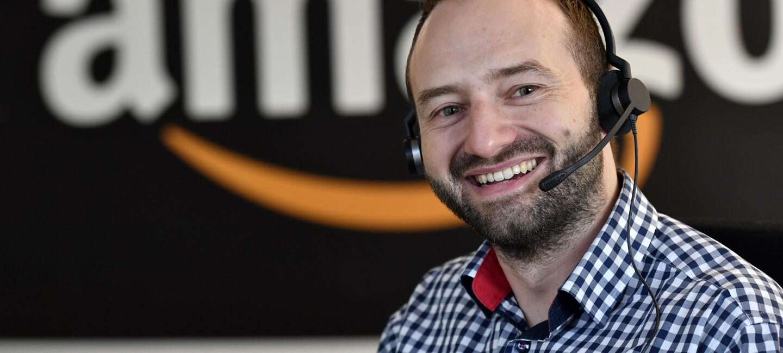 Ein dunkelhaariger Mann mit Bart und Headset lächelt in die Kamera. Er trägt ein kariertes Hemd. Im Hintergrund erkennt man etwas verschwommen das Amazon Logo.