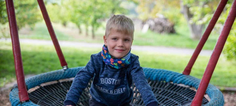 Jakob ist ein kleiner blonder Junger. Er schaukelt auf einem Spielplatz