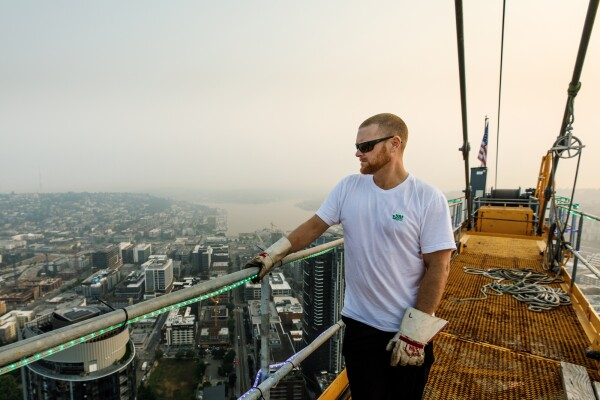 A man in a white t-shirt, black pants, sunglasses, and work gloves stands atop a crane high above Seattle, WA. Behind him, Lake Union is visible.