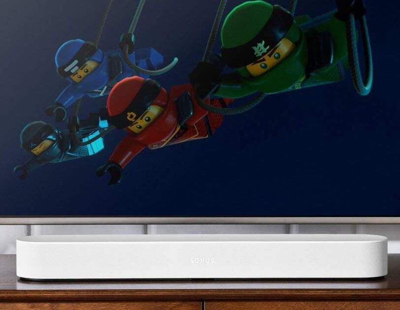 A television screen shows The Lego Movie, below the tv screen is a white Sonos Beam device. Both items sit on a television stand.