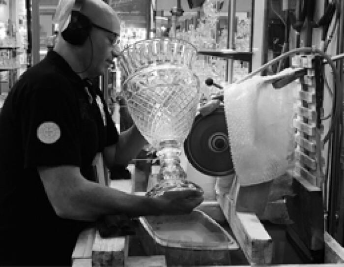 Un artisan est en train de polir un vase de cristal sur une machine électrique. Il porte un casque de protection sur les oreilles. Au fond on aperçoit des vitrines de créations en cristal. C'est une photo noir et blanc.