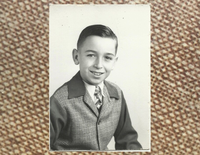 Rick Reefer at age 10. It's a black and white photograph and he is smiling and wearing a tweed jacket.