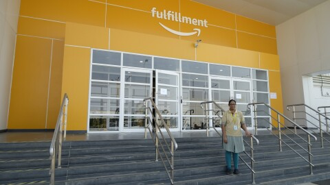 Merin, Amazon India's first forklift operator, stands on the steps that leads to the Fulfillment centre entrance