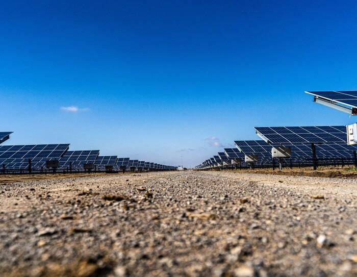 El proyecto solar de Alcalá de Guadaira en Sevilla es capaz de generar la energía necesaria para abastecer a 30 000 hogares españoles. Decenas de placas solares a lado y lado de la foto. En el centro un camino de tierra. El cierlo azul.