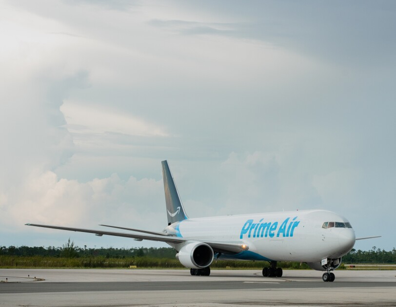 """A jetliner taxis on an airport tarmac. The plane says """"Prime Air"""" on the side and has an Amazon smile logo on its tail."""