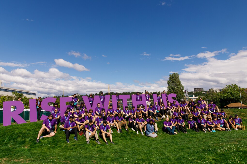 "Dozens of Amazonians in purple tees, pose on a hillside with giant letters that spell out ""rise with us,"" in support of the Special Olympics USA Games in Seattle, Washington."