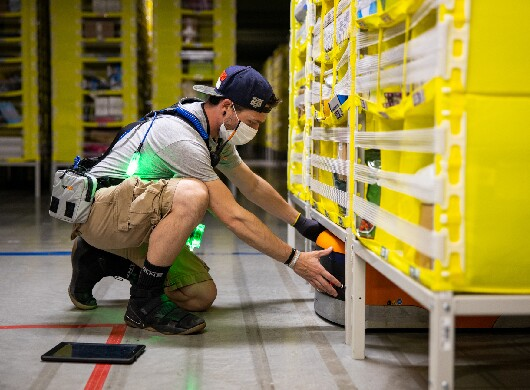 An Amazon employee works on a robot in an FC while wearing a safety vest
