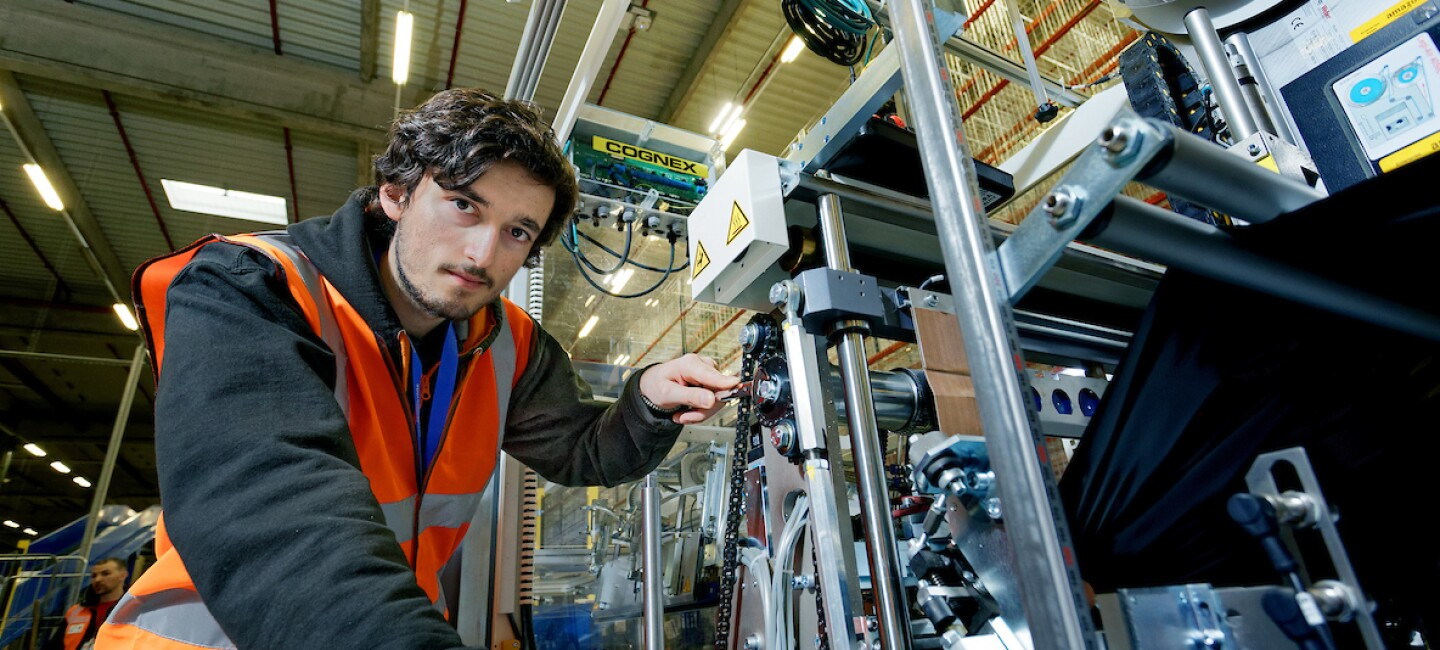 Reliability and maintenance engineering apprentice, Daniel Oulton, pictured looking into the camera which working on a machine