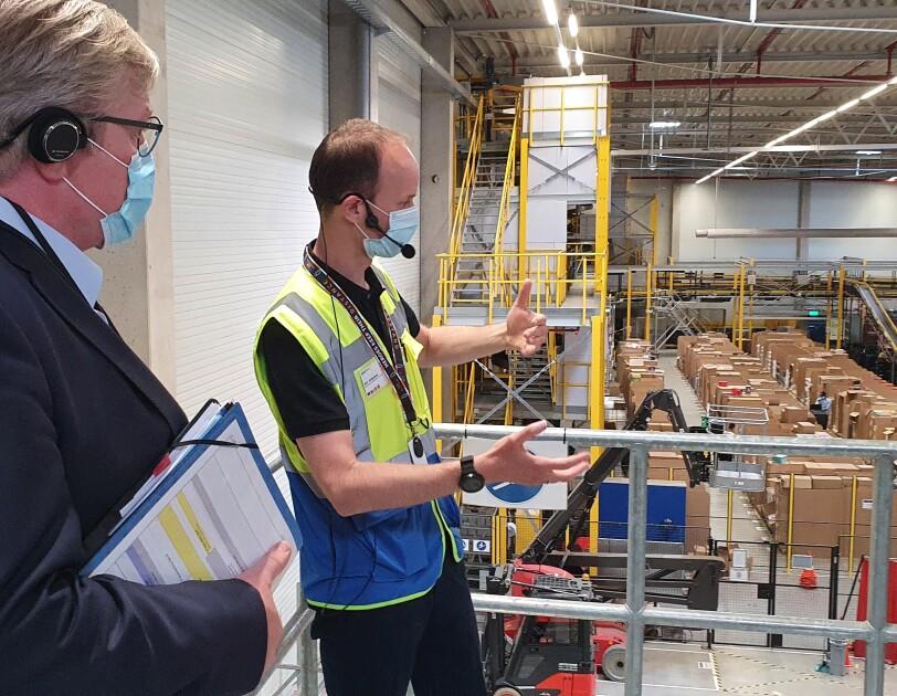 Ein Herr im blauen Anzug (links() mit einem Amazon Mitarbeiter in Sicherheitsweste: Beide stehen auf einer Ballustrade und blicken von oben in die Halle.