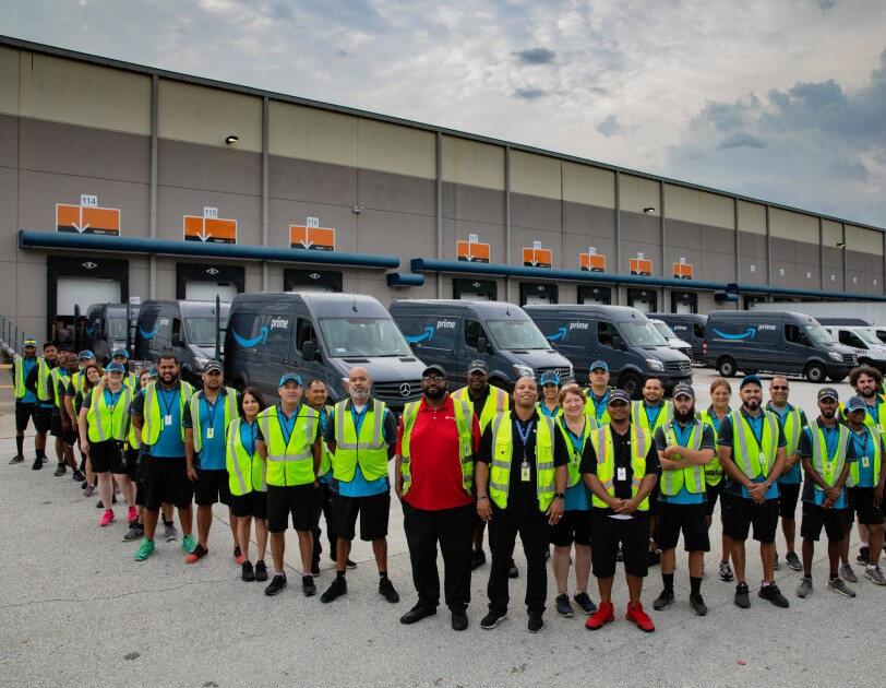 Dozens of people wearing safety vests stand in front of delivery vans decorated with the Amazon smile logo.