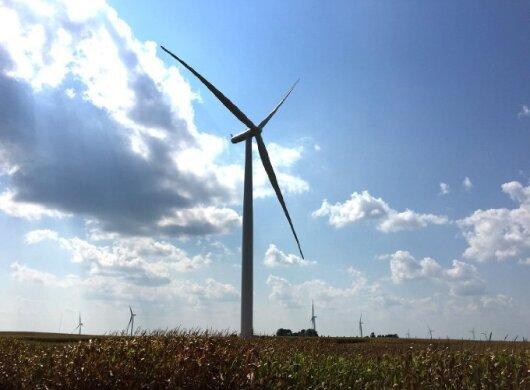 Une éolienne dans un champ, sur fond de ciel bleu avec quelques nuages. Au loin derrière elle, des arbres et une dizaine d'autres éoliennes