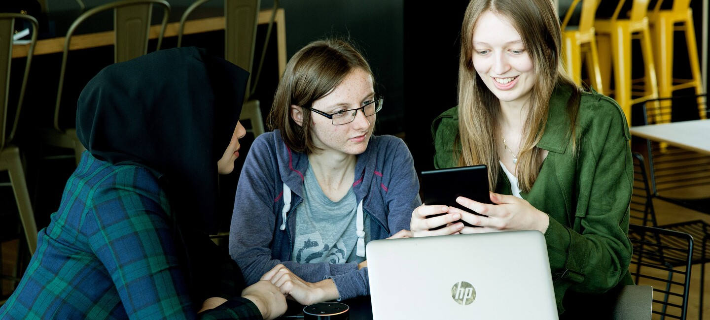Female Amazon bursary students sat together working on a digital device for Women in STEM