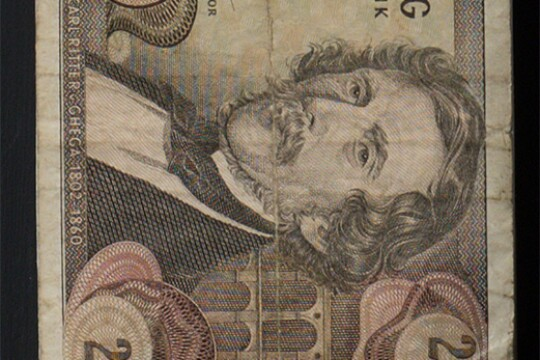 "Detail of a piece of old Austrian paper currency. The image includes the number 20 at the corners of the bank note as well as a well as a portrait of a man with a mustache. A label beneath the portrait says ""Carl Ritter v. Ghegha 1802 - 1860."""