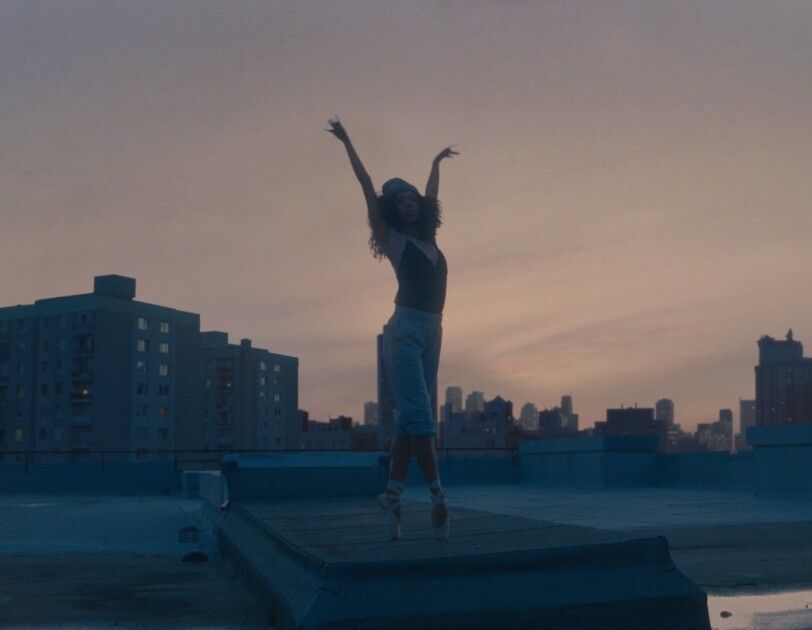 Ballerina stood on top of a rooftop with arms in air
