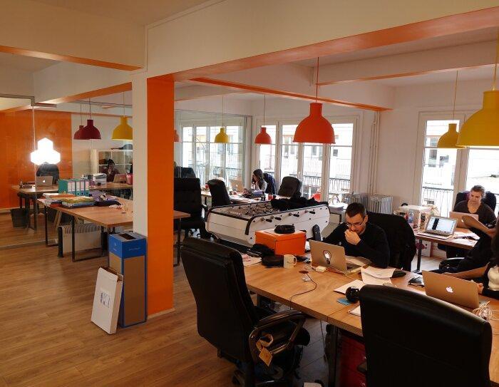 Des employés d'OpenClassrooms travaillent sur leur ordinateur dans un open space aux couleurs jaune et orange. On aperçoit un mur en miroir, de grandes fenêtres et un baby-foot au milieu des bureaux
