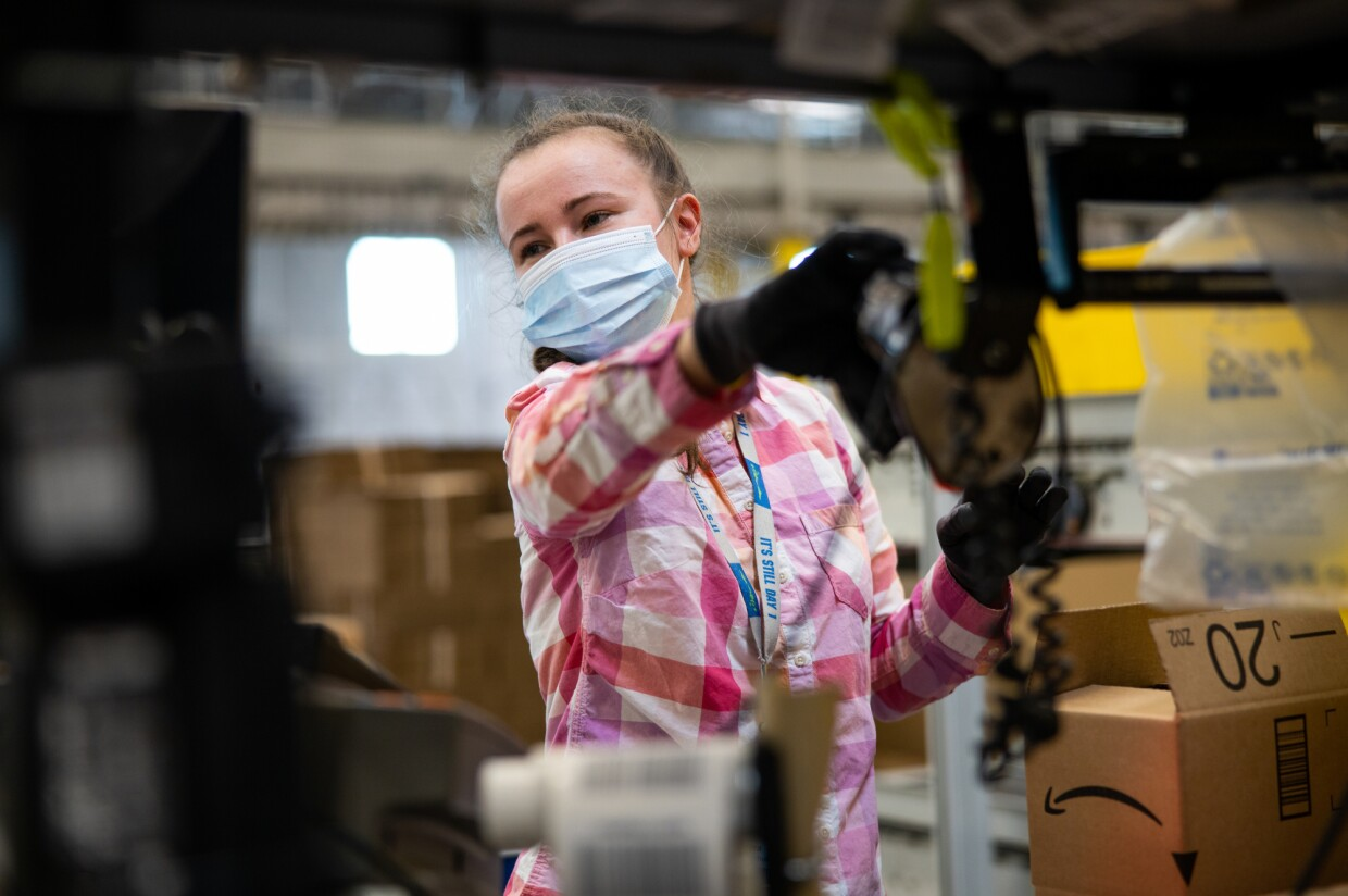 A woman works while wearing a mask. To her left, there is a cardboard box with the Amazon logo.