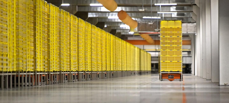 Ein Roboter transportiert ein gelbes Regal durch eine Halle. Links im Bild sind in einer langen Reihe weitere gelbe Regale zu sehen unter den Transportroboter sind.