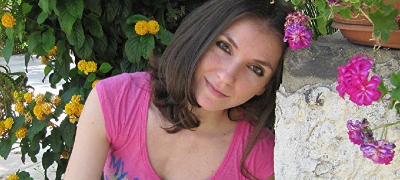 Ritratto di Elisa S. Amore, autrice di Kindle Direct Publishing. Sullo sfondo, dei fiori gialli.