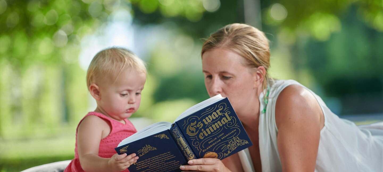 Eine Mutter liest auf einer Picknickdecke ihrem kleinen Kind etwas vor