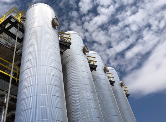Four metal cylindrical structures shown against a blue sky with clouds.