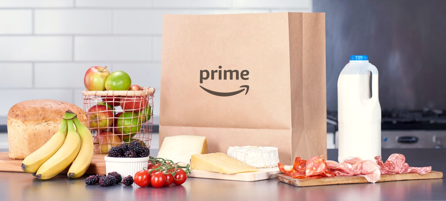 Paper bag with prime logo, milk carton and basket of fruit