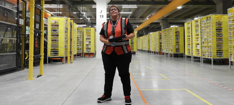 Die Amnesty Trainerin (schwarze Hose, grau-weiße Warnweste, Sicherheitsschuhe) ist in einer Logistikhalle zu sehen. Inder Hand hält sie ein Tablet. Hinter ihr sind zahlreiche gelbe Regale zu sehen, unter denen man Amazon Transportroboter erkennt.