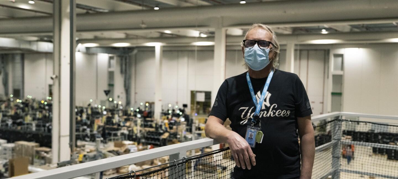 Un uomo in piedi ripreso a mezzo busto in un magazzino Amazon. E' poggiato ad una balaustra, indossa una maglia nera con una stampa 'Yankees' e un cordino con un badge al collo. Sul volto indossa una mascherina chirurgica.