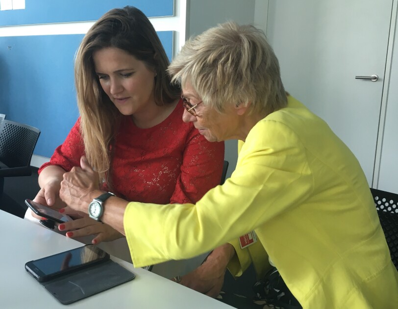 Eine  junge Frau erklärt einer älteren Dame, wie ein Smartphone funktioniert