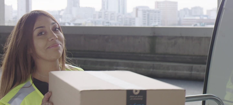 Une jeune femme en tenue de chauffeuse-livreuse tient dans ses mains un grand carton Amazon Prime, sur le site Prime Now de Paris. On apperçoit les immeubles de Paris en arrière-plan.