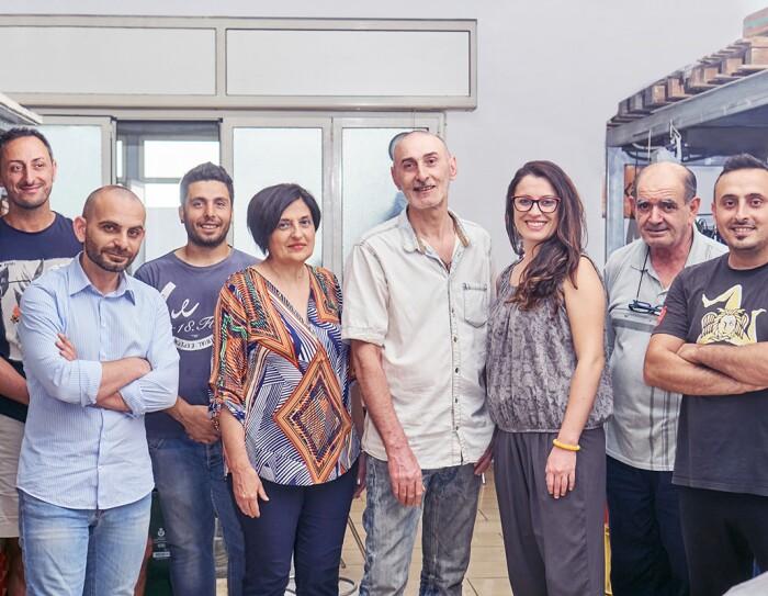 Foto del team di Kamira, formato da 8 persone in piedi, 6 uomini e 2 donne, tutti sorridenti, inclusi il fondatore Nino Santoro e la sua famiglia.