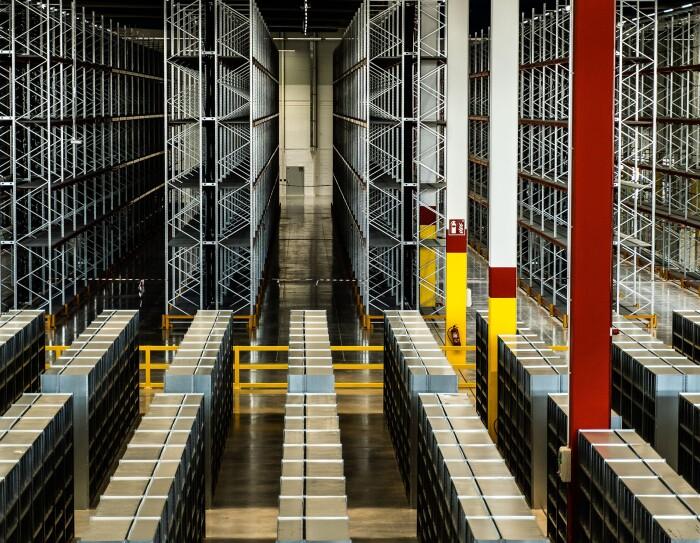 Imagen vertical del centro logísticos de Illescas. en primer plano aparecen estanterías para productos y al fondo estanterías mucho más altas para palés.