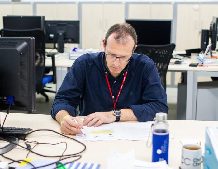 Durante un aperitivo virtual, a Hugo se le ocurrió cómo podía ayudar a Patrick con sus conocimientos de inteligencia artifical. Patrick está en el laboratorio del Institute for Research in Biomedicine de Barcelona. Patrick con unas gafas de color morado está sentado en su mesa de trabajo escribiendo en una hoja de papel. Lleva una camisa azul y un collar de color rojo para la acreditación. En la mano izquierda lleva un reloj. En la mesa también tiene un ordenador y un teclado, una botella de agua y una taza con alguna infusión. De fondo se ven más mesas, sillas y ordenadores, todo sin gente.