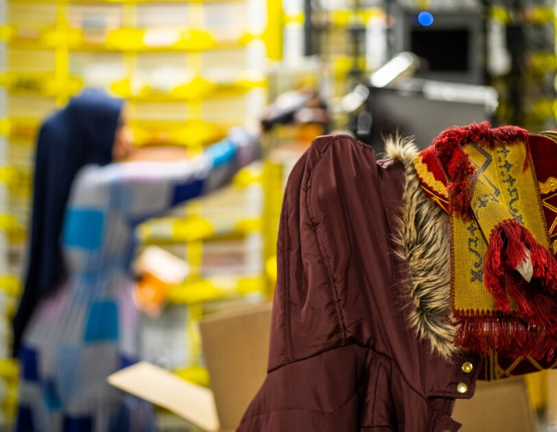 With a warehouse scene in the background of the photo, a winter jacket and a folded rug are hanging in the foreground. The rug is red and yellow.