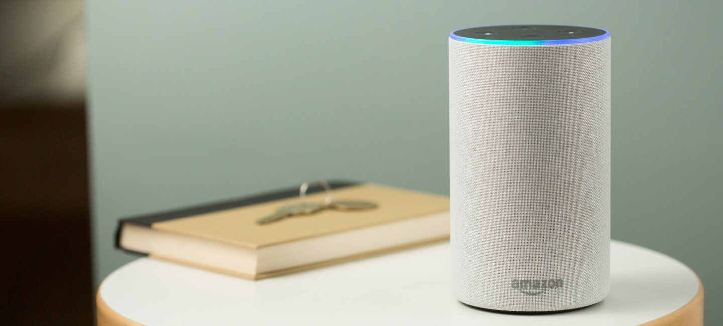 A white Amazon Echo sits on a table.