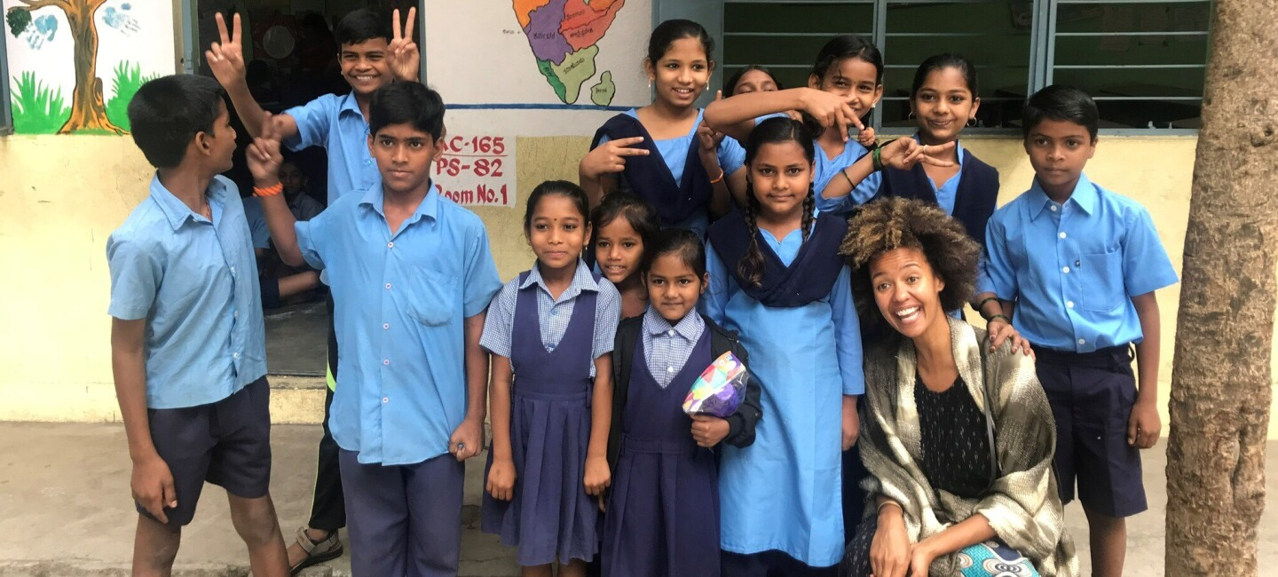 A group of 12 schoolchildren in Bangalore, India pose with an Amazon employee