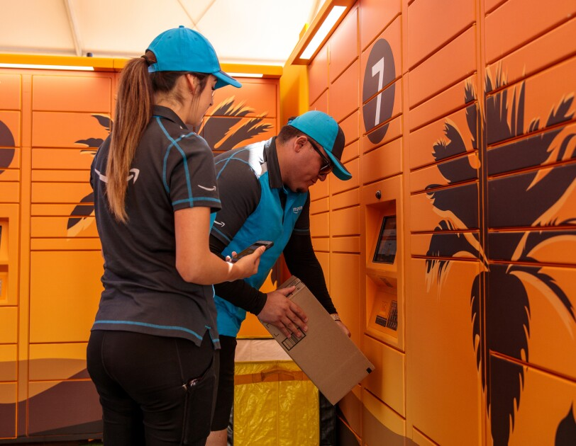 A man and a woman in delivery uniforms stand in front of a bank of lockers. The woman holds a phone. The man holds a box.