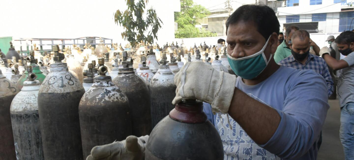 A man in India handling a tank of oxygen.