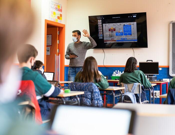 Alumnos del IES Josep Tarradellas en una clase con pizarra digital.  es una aula de un centro educativo. Aparacen 5 alumnos de espaldas, sentados en sus pupitres, vestidos con el uniforme de una sudadera de color verde. En la pared una pizarra digital  y  el profesor delante con una tableta en la mano derecha y la izquierda levantada. El profesor tiene barba y el pelo corto y un jersey de color gris y unos tejanos.